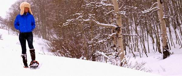Woman Snowshoeing Past Forest
