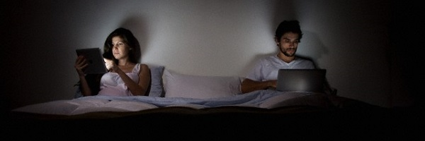 Couple in bed with laptop and tablet